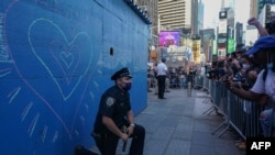 Un officier de police de New York met un genou à terre lors d'une manifestation à Times Square suite à la mort de George Floyd lors de son interpellation par un policier de Minneapolis le 31 mai 2020 à New York.