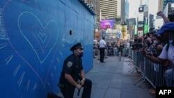 ຕຳຫຼວດນິວຢອກຄົນນຶ່ງ ຄູ້ເຂົ່່າລົງຢູ່ຕໍ່ໜ້າພວກປະທ້ວງ ຢູ່ຈະຕຸລັດ Time Square ທີ່ນະຄອນນິວຢອກ ຂອງການຕາຍ ທ້າວຈອຣຈ໌ ຟລອຍດ໌ ວັນທີ 31 ພຶດສະພາ 2020.