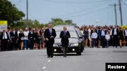 The hearse carrying Australian cricketer Phillip Hughes is followed by thousands following his funeral in Hughes' home town of Macksville, Dec. 3, 2014.