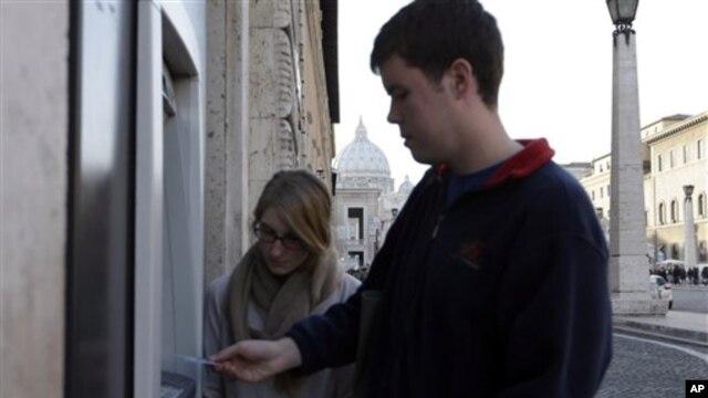 Seorang turis Amerika mengambil uang tunai di mesin ATM dekat kubah Basilika St. Peter, karena pembayaran elektronik sedang diblokir di Vatikan. (AP/Alessandra Tarantino)