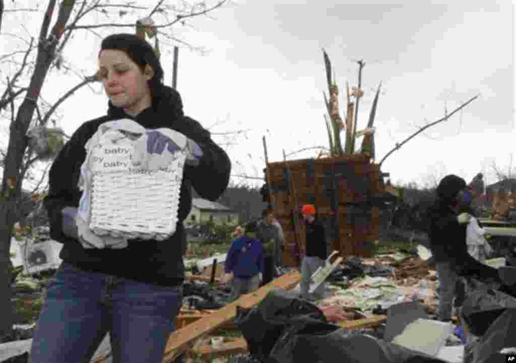 Stacey Loyd recovers her baby's personal items from her house after it was destroyed by a tornado on Friday that hit the village of Moscow, Ohio, Sunday, March 4, 2012.