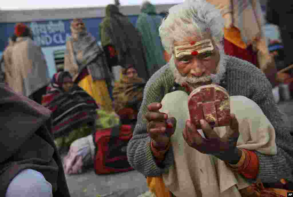 A Hindu holy man applies vermillion as he waits on platform 6 to leave the station in Allahabad, India, Feb. 11, 2013.