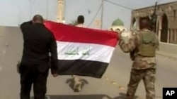 "This image made from Associated Press video shows Iraqi soldiers carrying an Iraqi flag to put on buildings, after a senior Iraqi commander declared that the city of Fallujah was ""fully liberated"" from Islamic State group militants, in Fallujah, Iraq, Sunday"