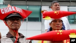 Protesters, wearing boat-shaped paper hats and mock missiles, join others in a rally at the Chinese Consulate to protest China's alleged continued militarization of the disputed islands in the South China Sea known as Spratlys, Feb. 10, 2018, in Makati city east of Manila, Philippines.