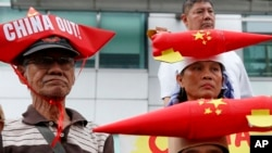 Protesters wearing boat-shaped paper hats and mock missiles, join others in a rally at the Chinese Consulate to protest China's alleged continued militarization of the disputed Spratly Islands in the South China Sea Feb. 10, 2018.