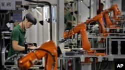 FILE - A man works amid orange robot arms at Rapoo Technology factory in southern Chinese industrial boomtown of Shenzhen. The country's trade with North Korea has slowed for the second consecutive year.