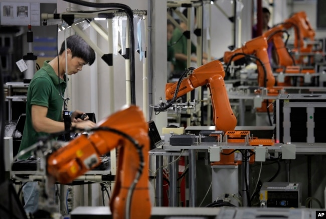 An employee works amid robot arms at a technology factory in the southern Chinese industrial boomtown of Shenzhen, Aug. 21, 2015. Chinese officials are calling on the U.S. to act responsibly on matters of taxation.