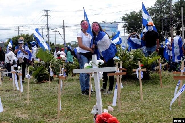 Manifestantes de pie junto a cruces en un monumento a las víctimas asesinadas en las recientes protestas contra el gobierno del presidente nicaragüense Daniel Ortega, durante una protesta en Managua, Nicaragua, el 4 de agosto de 2018. REUTERS / Oswaldo Rivas -