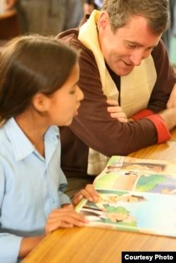 Pendiri Room to Read, John Wood, membaca dengan seorang anak di Nepal. (Andrea McTamaney)