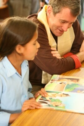 Room to Read founder John Wood reads with a girl in Nepal. (Andrea McTamaney)