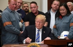 FILE - President Donald Trump signs a proclamation on steel imports during an event in the Roosevelt Room of the White House in Washington, March 8, 2018. He also signed one for aluminum.