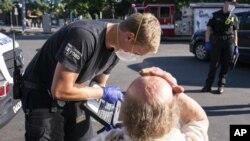 Ekipe hitne pomoći pomažu čoveku u Sejlemu, u Oregonu (Foto: AP/Nathan Howard)