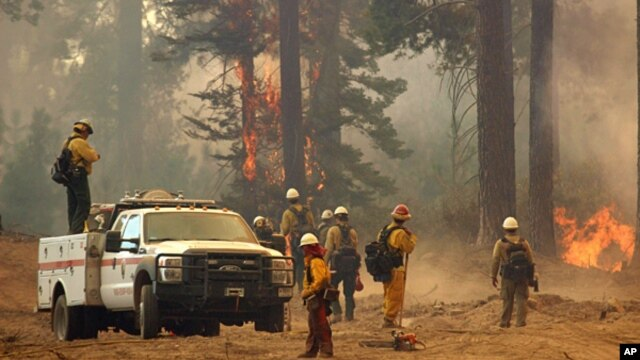 A fire crew stands watch along a fire break near a burn operation on the southern flank of the Rim Fire near Yosemite National Park in California, Aug. 30, 2013.