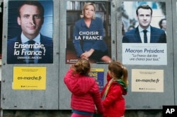 Children walk past election campaign posters for French centrist presidential candidate Emmanuel Macron and far-right candidate Marine Le Pen, in Osses, southwestern France, May 5, 2017. France is voting Sunday in the second round of the presidential elec