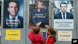 2017年5月5日,法国总统决选前,西南部奥赛的儿童走过马克龙和勒庞的总统大选海报。