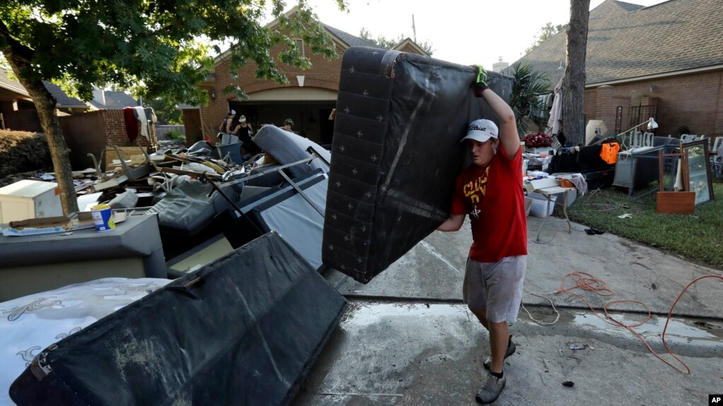 Tyler Moody removes a mattress from a friend's home after floodwaters recede from Tropical Storm Harvey