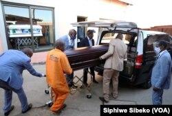 Des employés de Sopema Funerals placent le corps d'une personne décédée dans un corbillard à Soweto, au sud-ouest de Johannesburg, en Afrique du Sud, le 4 août 2020.