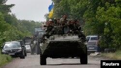 ທະຫານຢູເຄຣນ ງອຍຢູ່ເທິງລົດລຳລຽງພົນ ຂະນະທີ່ເຂົາເຈົ້າຂັບຜ່ານບ່ອນທີ່ພວກກະບົດນິຍົມຣັດເຊຍ ສັງຫານທະຫານຢູເຄຣນ 13 ຄົນຢູ່ເຂດຊານເມືອງ Volnovakha ຊຶ່ງຢູ່ທາງໃຕ້ ເມືອງ Donetsk (22 ພຶດສະພາ 2014)