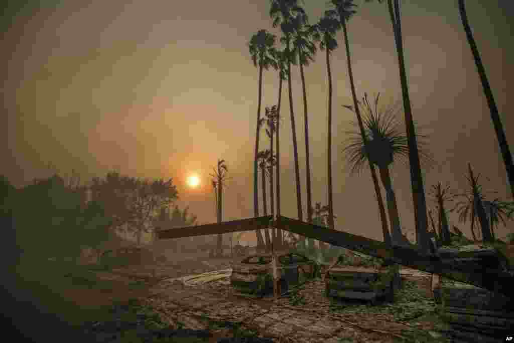 Smoke rises behind an apartment complex that has been leveled by flames as a wildfire ravages Ventura, California.