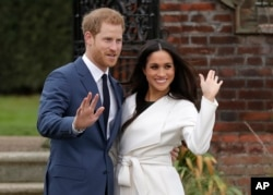 Britain's Prince Harry and his fiancee Meghan Markle pose for photographers during a photocall in the grounds of Kensington Palace in London, Monday Nov. 27, 2017.