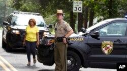 یک مامور ایالتی مریلند که جاده منتهی به محل تیراندازی را بسته است.