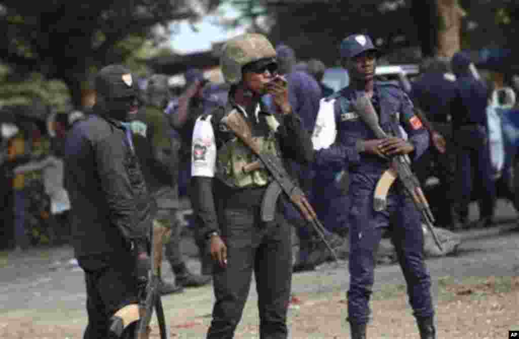 Ivory Coast policemen stand guard during a youth rally in Abidjan, Ivory Coast, 20 Dec 2010