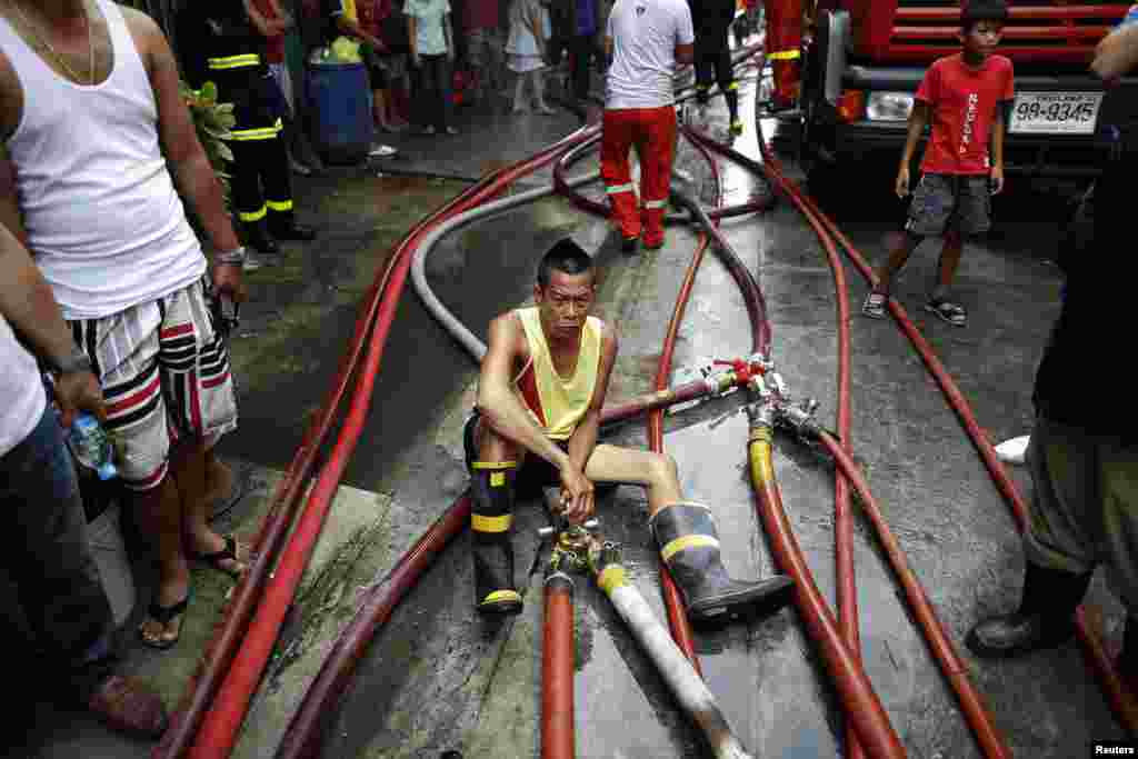 A man operates hoses as firefighters try to put out a fire in Bangkok's Sukhumvit area, Thailand. Dozens of houses were destroyed after a fire broke out in the residential area in central Bangkok.