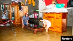 Residents move their belongings in a flooded house to higher ground in Vietnam's central province of Quang Binh October 18, 2011.