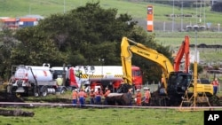 In this Sept. 15, 2017 photo, New Zealand Refinery staff work at the site of a jet fuel pipeline leak on a farm near Ruakaka in the North Island of New Zealand.