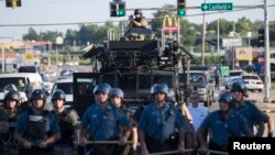 Riot police stand guard as demonstrators protest the shooting death of teenager Michael Brown in Ferguson, Missouri August 13, 2014.