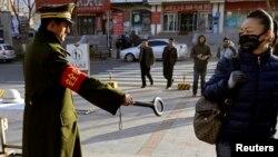 Cảnh sát Trung Quốc giơ máy dò vào một phụ nữ đi bộ trên đường phố ở Urumqi, Tân Cương.