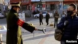 Seorang pejalan kaki mengamati seorang petugas keamanan yang tengah memeriksanya dengan alat deteksi saat melewati sebuah jalan di Urumqi, Xinjiang, daerah otonomi Uighur, China (17/12).