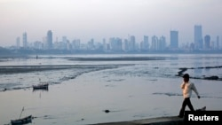 FILE - A man walks along a wall overlooking the central Mumbai financial district skyline.