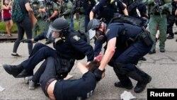 Baton Rouge kentinde polis bir göstericiyi gözaltına alırken zor kullanıyor.