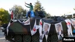 A man poses on an armored vehicle with portraits of Turkish President Recep Tayyip Erdogan parked outside the parliament building in Ankara, Turkey, July 16, 2016.