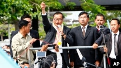 Sam Rainsy, leader of the opposition Cambodia National Rescue Party (CNRP), delivers a speech from a vehicle upon his arrival at Phnom Penh International Airport in Phnom Penh, July 19, 2014.