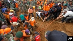 印尼救援人員徒手和使用簡易工具在泥土和瓦礫中搜尋。