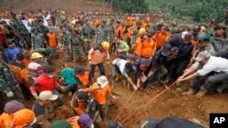 救援者试图在泥石流中挪出尸体