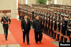 FILE - North Korean leader Kim Jong Un and Chinese President Xi Jinping inspect honor guards in Beijing, in this undated photo released by North Korea's Korean Central News Agency (KCNA) in Pyongyang, March 28, 2018.