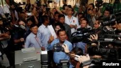 柬埔寨選民星期天投票,已經執政三十多年的首相洪森(中)在金邊郊區的電視台投票。