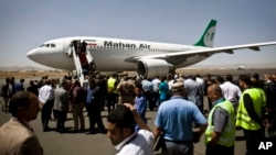 FILE - Yemeni airport security and transportation officials greet a plane from the Iranian private airline, Mahan Air after it lands at the international airport in Sana'a, Yemen.
