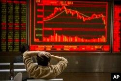 Un inversor chino observa la caída de los precios de las acciones en una financiera en Beijing. Feb. 9, 2018