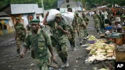 FILE - In this Nov. 30, 2012 file photo, M23 rebels withdraw from the Masisi and Sake areas in the eastern Congo town of Sake, some 27 kms west of Goma, Congo.