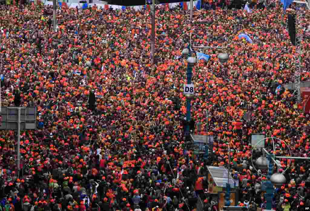 A crowd gathered in Dam Square to watch as King Willem-Alexander, Queen Maxima and Princess Beatrix sign the act of abdication in the Royal Palace in Amsterdam, the Netherlands.