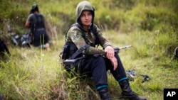 FILE - Juliana, a 20-year-old rebel fighter for the 36th Front of the Revolutionary Armed Forces of Colombia, or FARC, rests from a trek in the northwestern Andes of Colombia, in Antioquia state, Jan. 6, 2016.