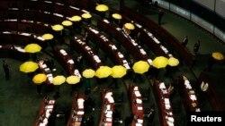 Các nhà lập pháp Hong Kong ủng hộ dân chủ cầm những chiếc dù mầu vàng, biểu tưởng của phong trào Chiếm Trung rời khỏi phòng họp như một cử chỉ tẩy chay chính phủ Hong Kong 7/1/15