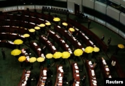 FILE - Pro-democracy lawmakers carrying yellow umbrellas, symbols for the Occupy Central movement, leave in the middle of a Legislative Council meeting as a gesture to boycott the government in Hong Kong, January 7, 2015.