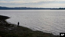 FILE - A fisherman walks on the shore of the fishing village Quetalmahue in Chile's Chiloe island, May 10, 2016. Scrub typhus has been confirmed in a cluster of cases on the island, far from places it usually strikes.