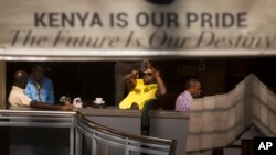 A man takes photographs of the mall with his smartphone while he sits in a cafe at the reopened Westgate Shopping Mall in Nairobi July 18, 2015. (AP Photo/Ben Curtis)