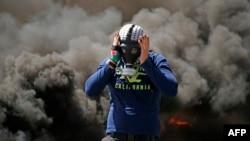 احتجاج کے دوران ماسک پہنے ہوئے ایک فلسطینی شخص ٹائر جلا رہا ہے